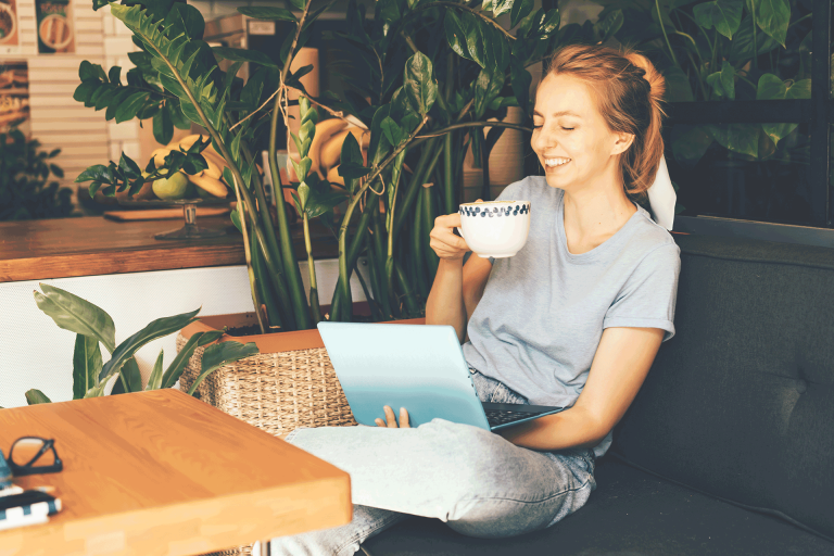happy young women enjoying her life learning something new at her lap top sipping coffee