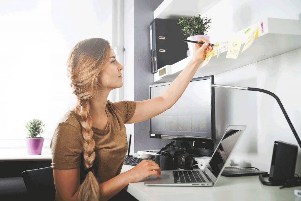 woman-working-on-computer-at-home-office-writing-down-goals